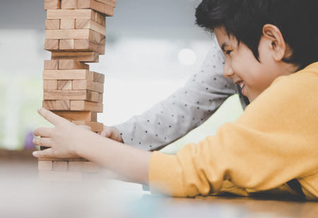 Boy is building toy block tower with friend