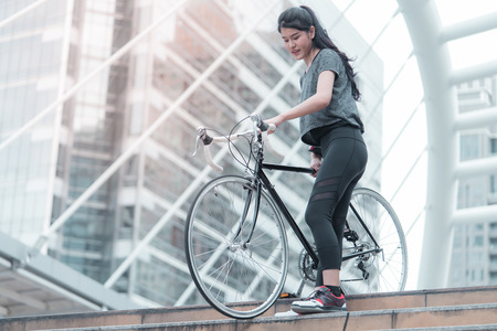Sport woman is carrying her bike down the stair