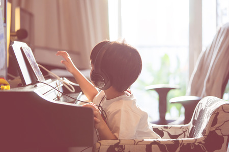 Little Boy is playing with piano and Music Tablet at home, Children Music Education concept.