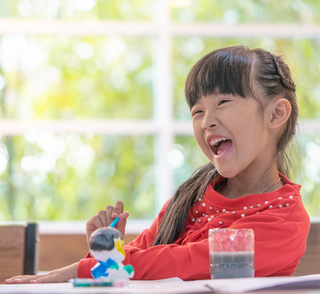 Laughing girl is painting a doll in Art classroom, for creativity concept Stock Photo