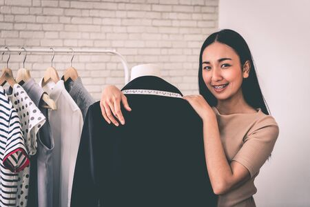 Female fashion designer tailor is measuring office suit jacket