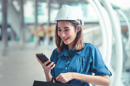 Young engineer woman is using mobile in a modern city