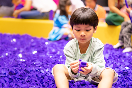 boy is playing with purple educational toy block