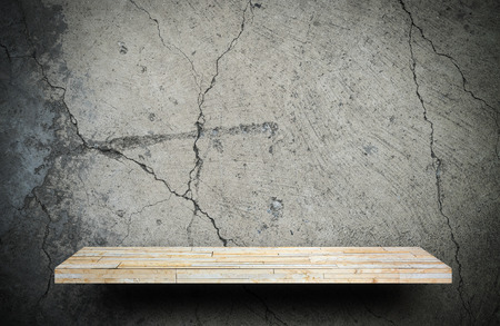 Blank rock stone display shelf on crack cement wall Stock Photo