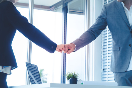 Business man and woman business couple fist bump hand together for team work