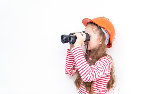 Kleine meisjesontdekkingsreiziger kijkt door een verrekijker