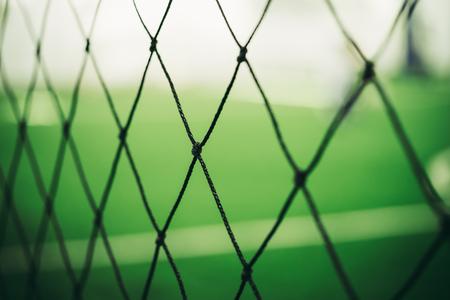 Soccer training net blur on training ground with children
