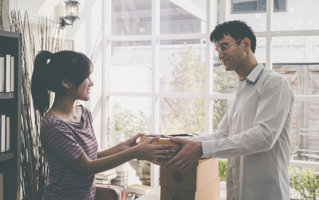 man is handing packages to a woman Stock Photo - 112410959