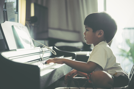 Little Boy is playing with piano and Music Tablet at home Foto de archivo - 112674613