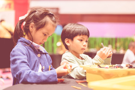 Asian girl and boy is playing with educational toy
