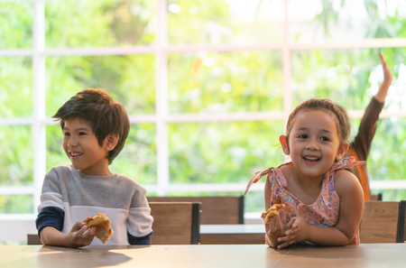 Kindergarten students hand up for more pizza