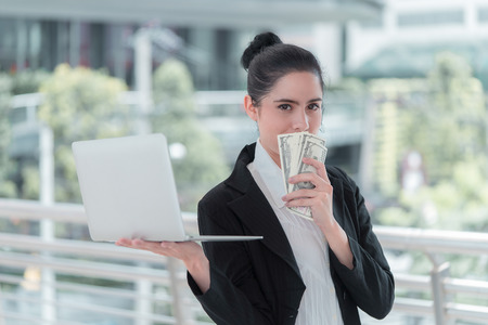 Business woman is making cash online on laptop