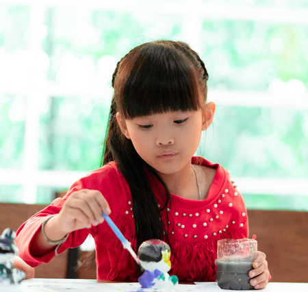 Asian girl is painting a doll in Art classroom, for creativity concept