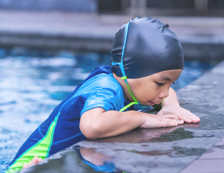 Wet suit Asian boy with swim glasses is swim in a pool
