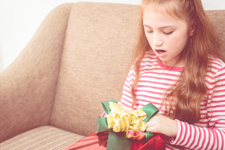 Female kid is opening surprise present christmas box Stock Photo