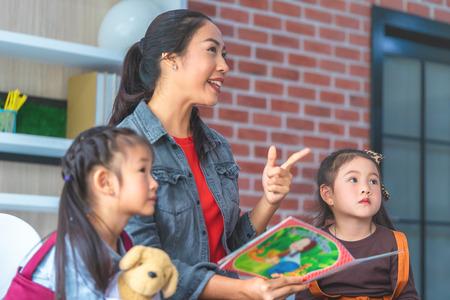 Teacher is reading story book to kindergarten students pointing 版權商用圖片