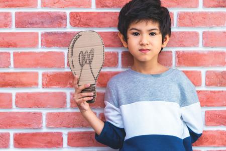 Little boy holding paper idea bulb on brick background Banque d'images - 112421957