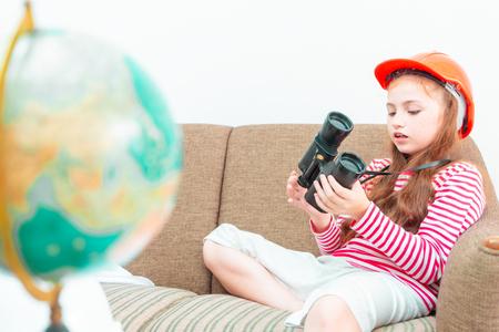 Little girl explorer is looking through binoculars