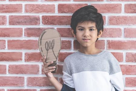 Little boy holding paper idea bulb on brick background Banque d'images - 116227616