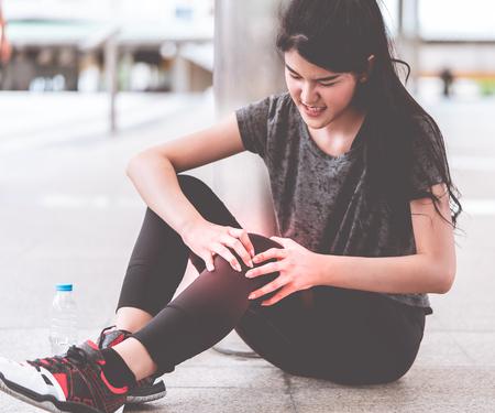 Sport woman is having an injury on her knee legs Reklamní fotografie