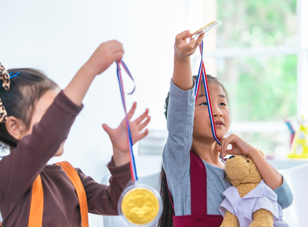 Little girl is holding gold medal for student award Stock Photo
