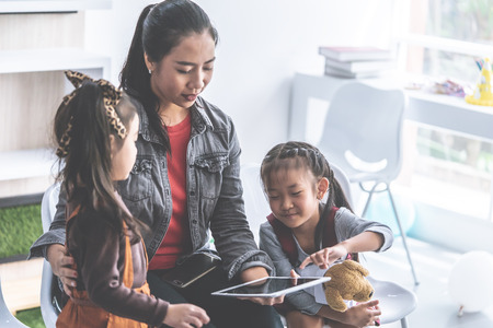 Teacher is reading story book to kindergarten students with tablet 版權商用圖片