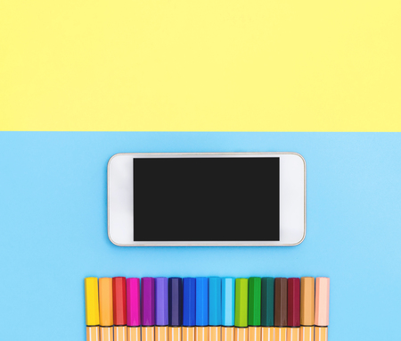 blank mobile phone and Color Marker pen line up on blue and yellow