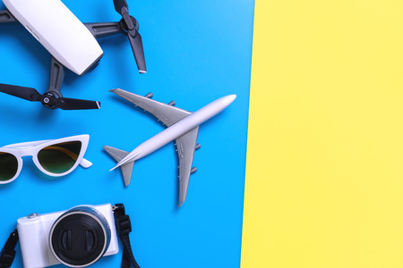 Hi tech travel gadget and accessories on blue and pink yellow copy space