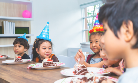Asian children is happy eating her birthday cake in party Reklamní fotografie