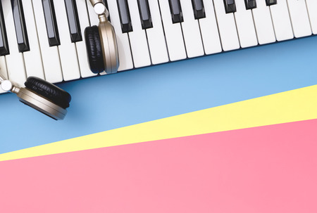 Music keyboard synthesizer with golden headphone on blue pink copy space
