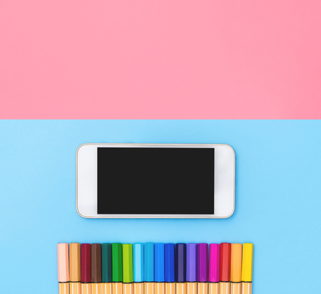 blank mobile phone and Color Marker pen line up on blue and pink