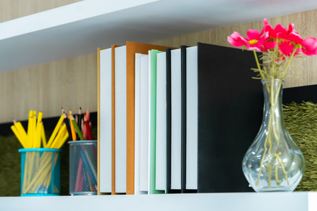 Classroom book shelf with books flower and pencil