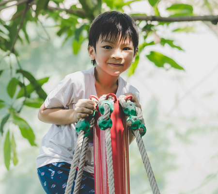 Asian boy is climbing on rope pole in playground Banque d'images - 117213105