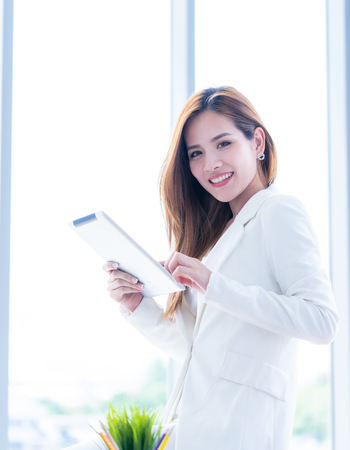 Asian woman in white is using tablet in office space