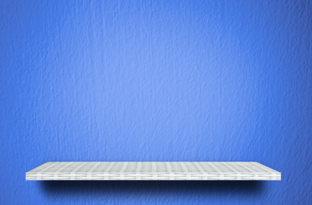 Empty white shelf on blue cement background for product display Stock Photo