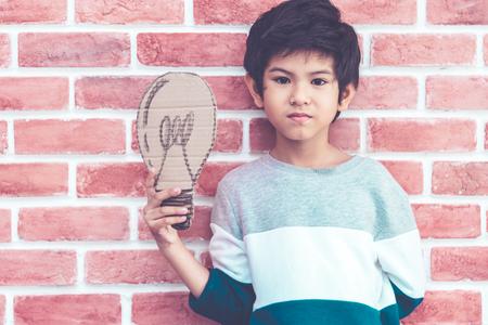 Little boy holding paper idea bulb on brick background Banque d'images - 123519954