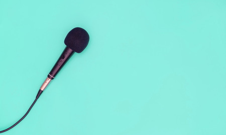 Black microphone on blue teal background for music concept