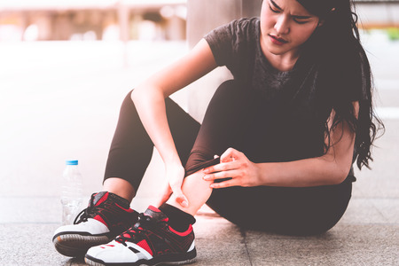 Injury from running concept, asian woman holding her ankle with pain Stock Photo