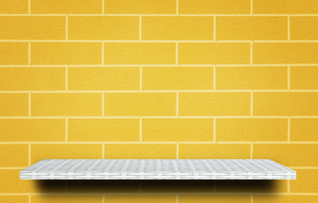 Empty top white shelves yellow brick wall background product display