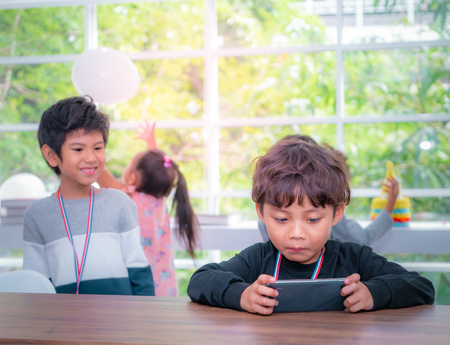 Two Little boys are playing online game on mobile phone
