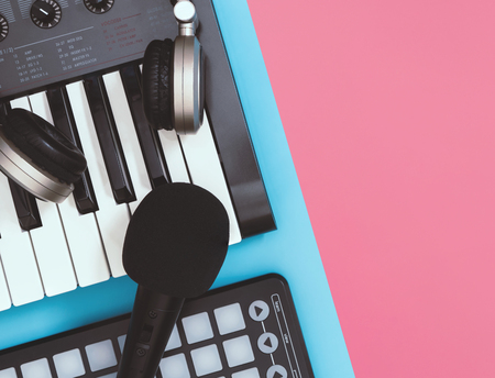black microphone and headphones on table top view blue and pink background for copy space