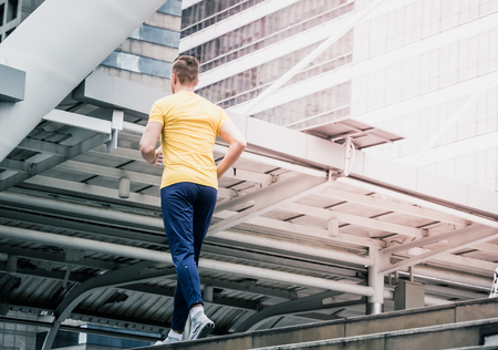 shot of young man in yellow jogging out in modern city. male runner working out in modern city. Stock Photo
