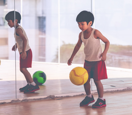 little kids are playing soccer football for exercise at home