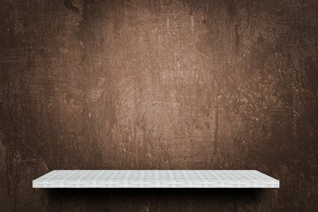 Empty white shelf on grunge brown background for product display