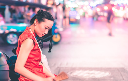 Chinese girl is traveling in China town street Thailand Bangkok with tuk tuk cart on background