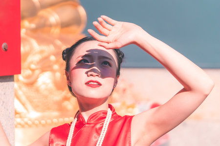 Chinese woman is holding hand up to protect from the sun