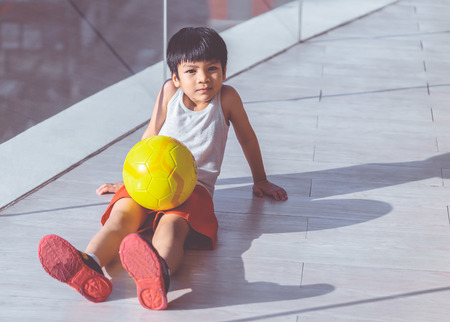 Young boy is sitting with soccer and smiling