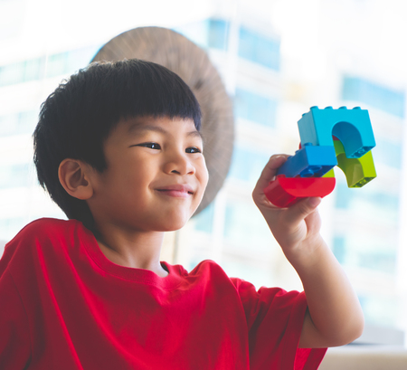 Happy boy stacking Toy blocks on a living room for educational toy 写真素材