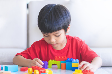 Garçon jouant des blocs de jouets dans le salon avec la main jusqu'à dire bonjour