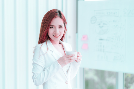 Young Asian woman in white is taking a break with hot coffee